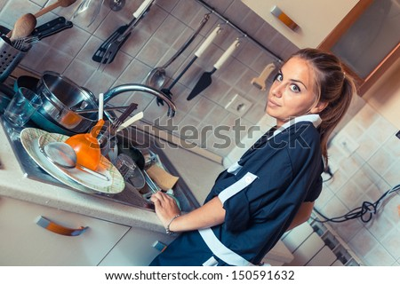 Housemaid Washing Dishes in the Kitchen - stock photo
