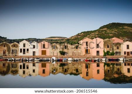 Houses along the coast with reflection in bosa, sardegna, Italy - stock photo
