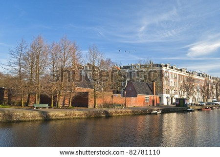 houses and boats along a canal in Amsterdam