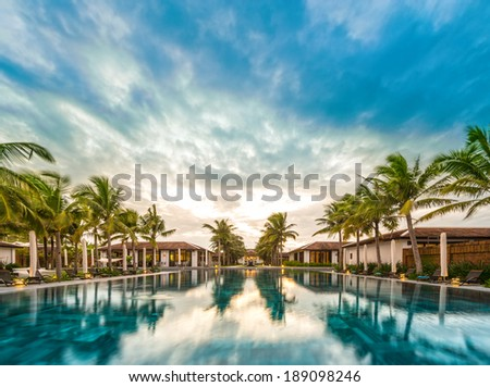 Houses and pool in middle of resort in Vietnam, Asia. Reflection of green palms and blue sky with clouds in water. Beautiful tourist resort. Modern architecture, luxury exterior. Bright summer day. - stock photo