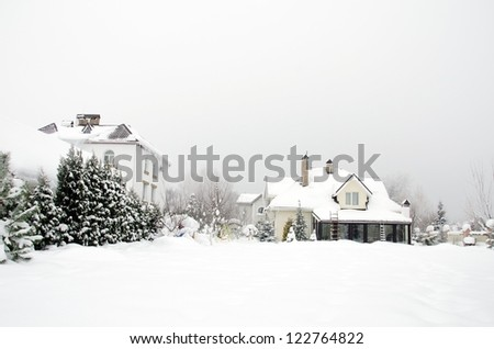 houses and their gardens under snow in winter - stock photo