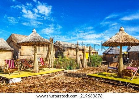 Houses and umbrellas made out of reeds on Uros floating islands on Lake Titicaca near Puno, Peru - stock photo