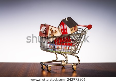 Houses are stacked in a shopping cart. - stock photo