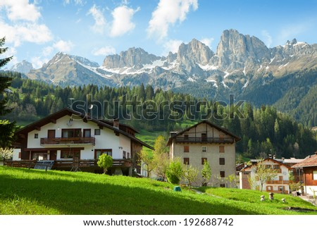 Houses are surrounded by the Dolomites, Comune di Falcade, Italy.  View of a typical alpine residential structure.  - stock photo