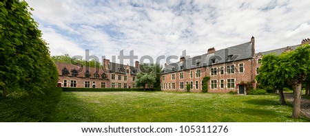 Houses in traditional architecture stand around blossoming meadows. - stock photo
