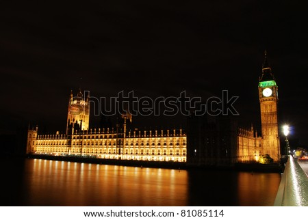 Houses of Parliament and big ben seen at night across the river Thames. London, UK - stock photo
