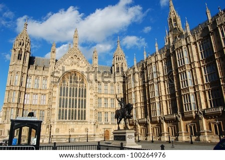Houses of Parliament with a statue in front of it, London, England - stock photo