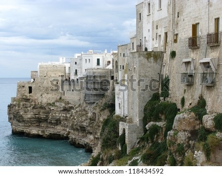Houses on the rocks of the coast of Polignano a mare at the Mediterranean in Italy - stock photo