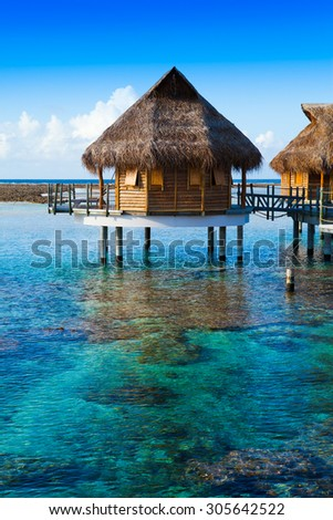 houses over the transparent quiet sea water. Tahiti - stock photo