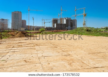 Houses under construction and cranes on the construction site - stock photo