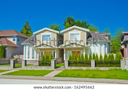 Houses with nicely landscaped and trimmed front yard in the suburbs of Vancouver, Canada.