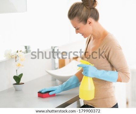 Housewife cleaning desk in bathroom - stock photo