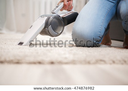 Housewife cleaning fluffy carpet in living room