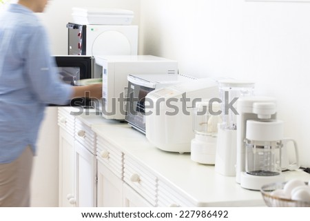 Housewife cooking in a small cooking appliances - stock photo