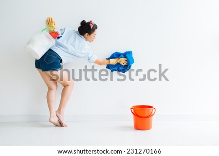 Housewife in denim shorts cleaning the wall  - stock photo