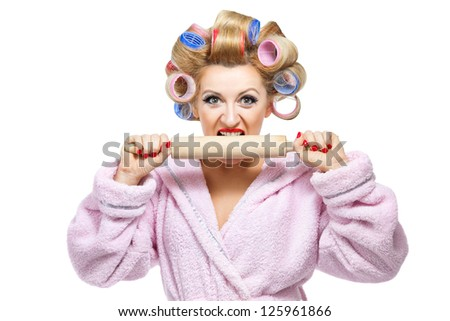 Housewife in pink bathrobe biting rolling pin on white background