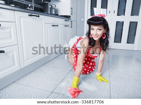 Housewife is cleaning floor in kitchen - stock photo