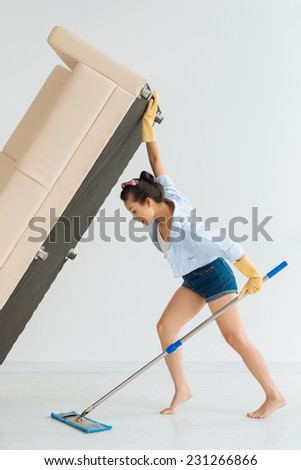 Housewife lifting sofa to wipe underneath the floor - stock photo