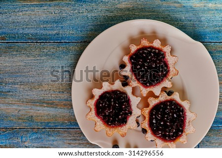 Housewife prepared tarts made from unleavened dough top with them waiting for the mix of ripe berries gathered in the garden, bilberry, blueberry, black currant and cherry - stock photo