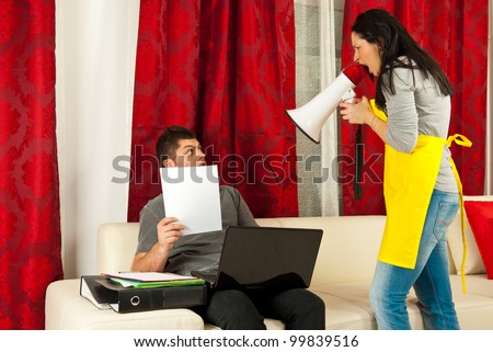 Housewife shouting by megaphone to her husband who working to much from home - stock photo