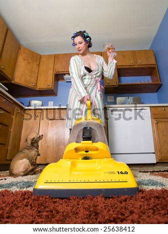 housewife vacuuming in the kitchen while drinking - Domestic series - stock photo