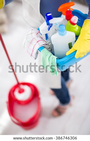 Housewife wears bucket with chemicals, cloths and mop for cleaning house - stock photo