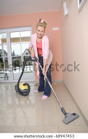 housewife with vacuum cleaner - stock photo