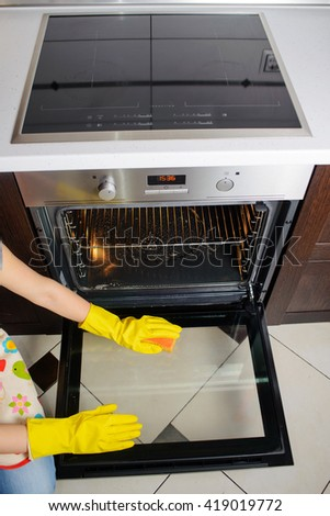 housework and housekeeping concept - close up of woman hand in protective glove cleaning door of electric oven - stock photo