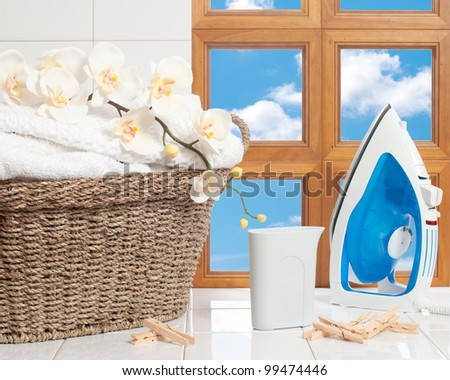 Housework concept with fresh laundry and iron against a window with blue sky - stock photo