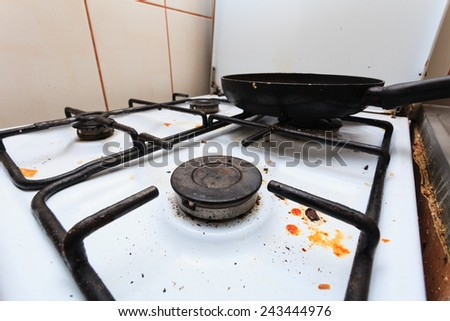 Housework, hygiene and cleaning concept. Dirt at home. Dirty filthy gas stove with used kitchen cooking stuff, frying pan - stock photo