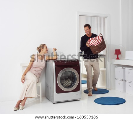 Housework, young woman and man doing laundry - stock photo