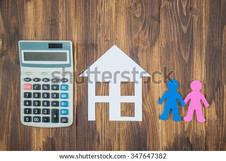 housing and mortgage for young families. couple dreaming, paper house with calculator - stock photo