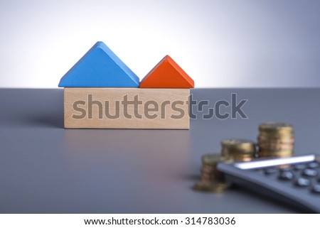 Housing Loan concept. House Wooden Block, coins and calculator  - stock photo