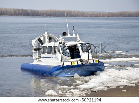 Hovercraft is on the icy shore waiting for passengers to carry across a river. - stock photo