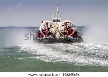 Hovercraft traveling away across sea - stock photo