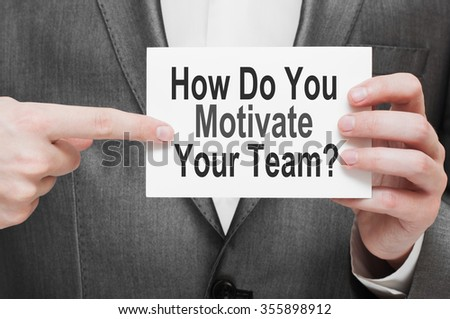How Do You Motivate Your Team ? Businessman holding a card with a message text written on it - stock photo