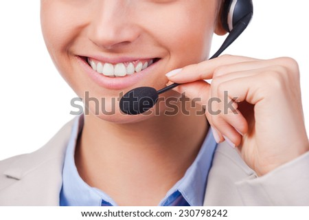 How may I help you? Close-up of young customer service representative adjusting her headset and smiling while standing against white background - stock photo