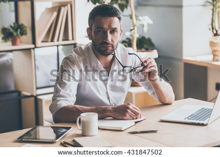 How may I help you? Confident mature man carrying his eyeglasses and looking at camera while sitting at his working place in office  - stock photo