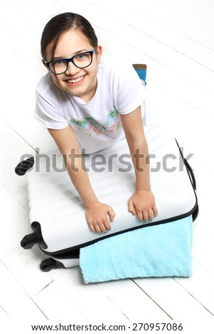 How to pack a suitcase? Girl suitcase packed with things for a holiday trip  - stock photo