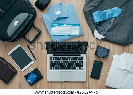 How to pack for a business trip: all items that needs to be packed, a bag and a laptop on a desktop, travel concept