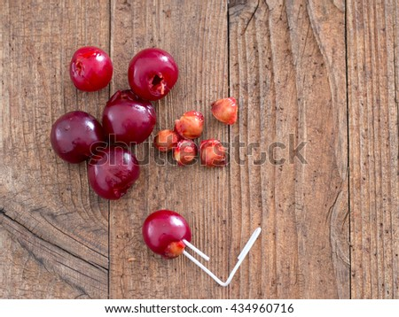 How to remove sour cherry pips, stones with a paperclip. Practical hack. On rustic wooden board. - stock photo
