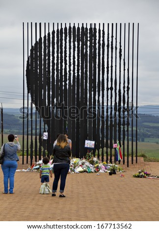 Howick, KwaZulu-Natal, South Africa - 15 December 2013: Mourners gather to pay their respects to the deceased Nelson Mandela at the site where the former political activist was captured in 1962.