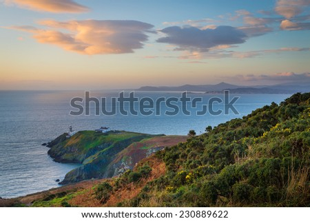 Howth cliffs vegetation and Baily Lighthouse at golden hour - stock photo