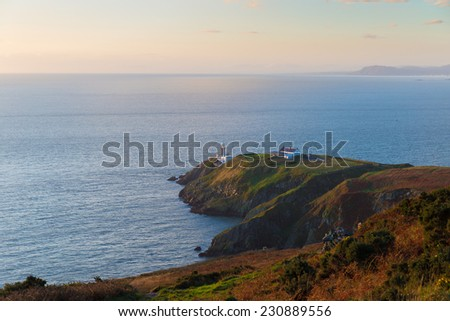 Howth cliffs with helipad and Baily Lighthouse at golden hour - stock photo