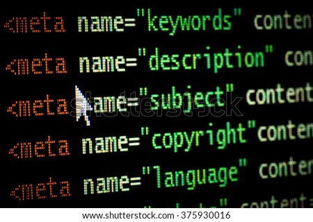 HTML web page computer programming code meta tags in red light and dark green with mouse pointer on black background seo optimization ranking search engines - stock photo