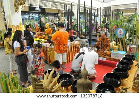 HUA HIN - APRIL 14: Visitors to a shopping mall take part in a merit making ceremony while celebrating the Thai New Year, or Songkran, on April 14, 2013 in Hua Hin, Thailand. - stock photo