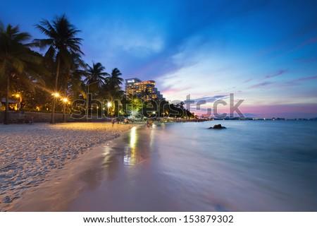 Hua Hin beach at twilight with cloudy sky - stock photo