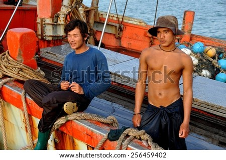 Hua Hin, Thailand - December 31, 2009:  Two Thai fishermen on deck of their boat docked at the Hua Hin public fishing pier - stock photo