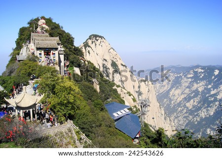 Huashan Mountain North Peak. Scenic rocky forested cliffs. Cable way station, buildings and pavilions on mountain ridge. Crowd of people walking. Sunny autumn day of October 05, 2014. Shaanxi, China.