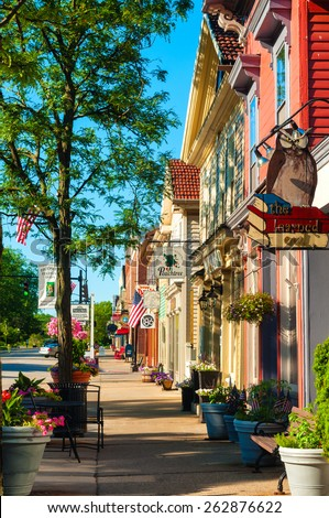HUDSON, OH - JUNE 14, 2014: Quaint shops and businesses, anchored by the popular Learned Owl bookstore at right, go back more than a century give Hudson's Main Street a charming and inviting appeal. - stock photo